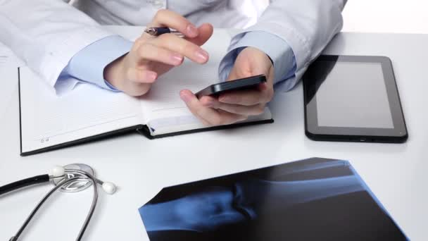 Doctor texting on mobile phone and notes something, white