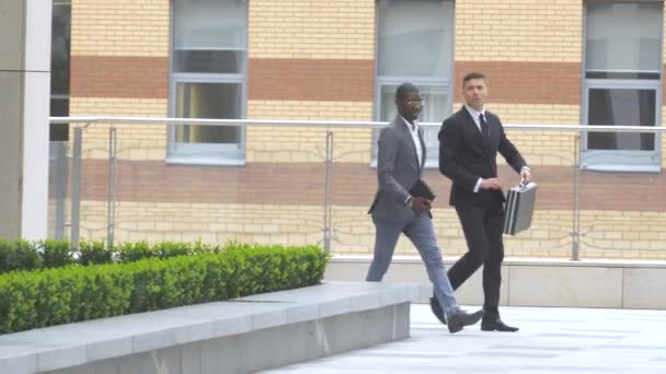 African American businessman walking on the street near office building