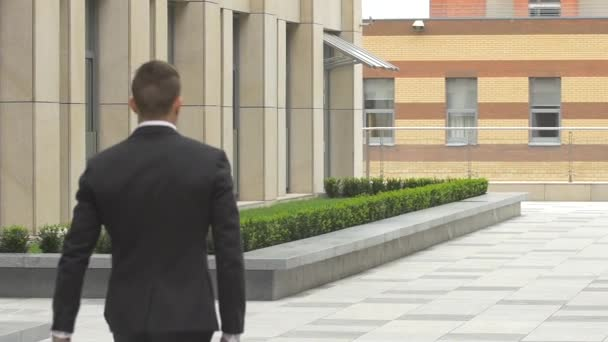 back view of walking businessman on the road over beautiful landscape. slow motion