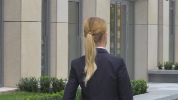 elegant blonde business woman with tablet computer goes around office building. slow motion