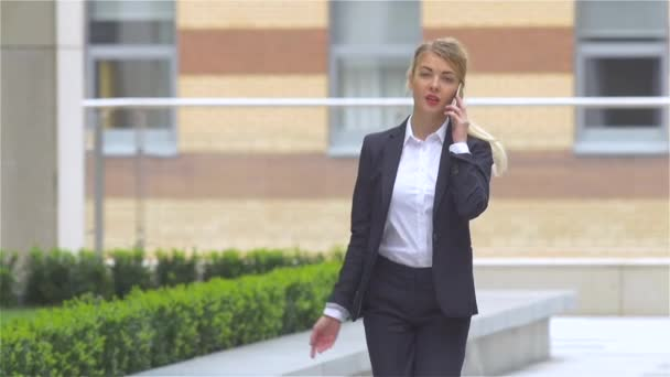 Successful blond woman talking on cellphone while walking outdoor. slow motion