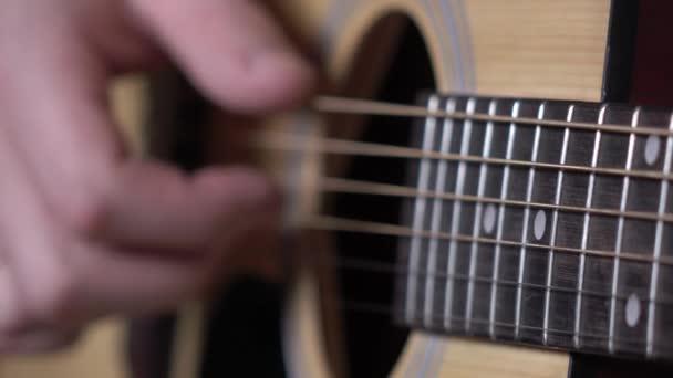 Ruka člověka, hrát na kytaru, zaměření na smyčce, zblízka