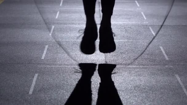 Person jumps on the jumping rope, feet in silhouette, front view