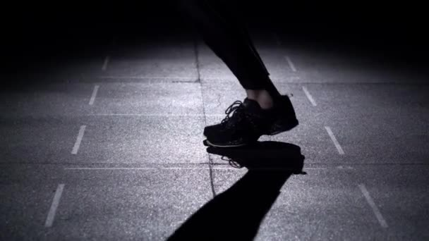 Person jumps on the jumping rope, feet in silhouette, slow motion