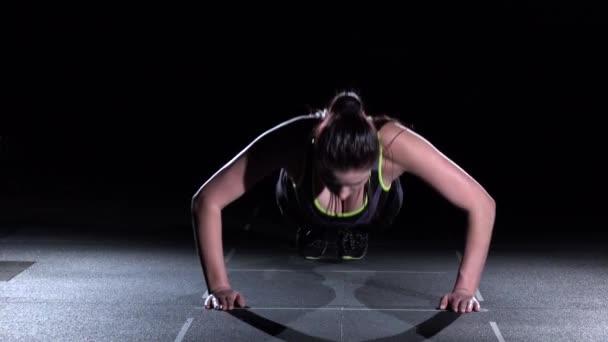 Mladá žena, která dělá kliky v tělocvičně na černém