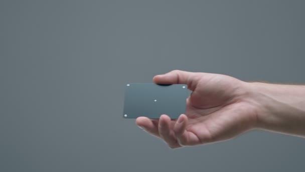 Detailní záběr mužské ruky dává plastové kreditní karty se sledovacími body na ženské rameno na šedém pozadí studia