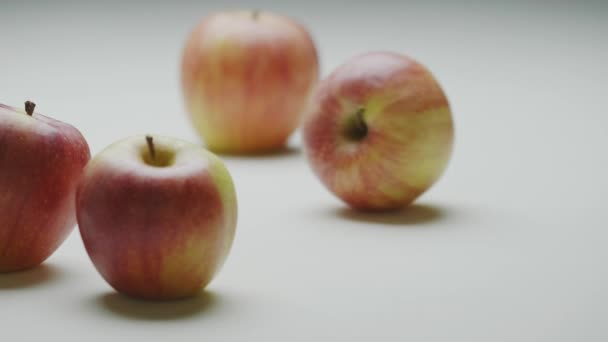 Red-yellow apples organic natural fruits moving on surface, strike and stop, close up studio video