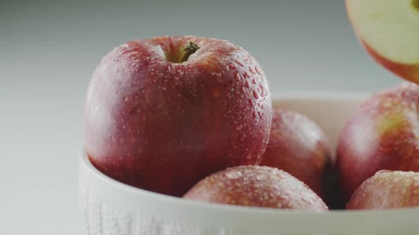 Hand put half of tasty natural apple in waterdrops on heap of organic red whole fruits, close up studio video