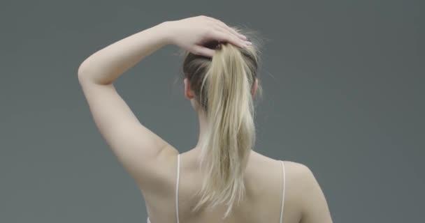 Csinos fiatal szőke nő hosszú hajjal vegye le surlókór, engedje le a hajat a mindennapi szépség rutin, vissza nézet