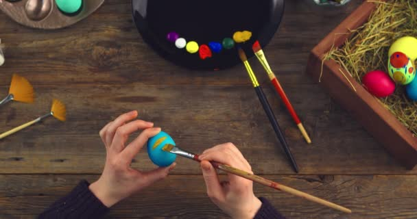 Happy easter. Top view video of female artists hands painting on eggs for christian religious holiday on wooden table