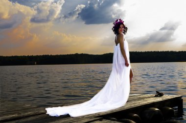 Young woman wrapped in a white organza, is on the boardwalk, like an angel, against the evening sunset and the water surface of the river, on a head a wreath of orchids, the girl is glowing. Art processing. Dryad or fairy.