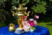 Fotografie The end of the summer. Samovar, cups of tea and autumn gifts - flowers, vegetables and fruit
