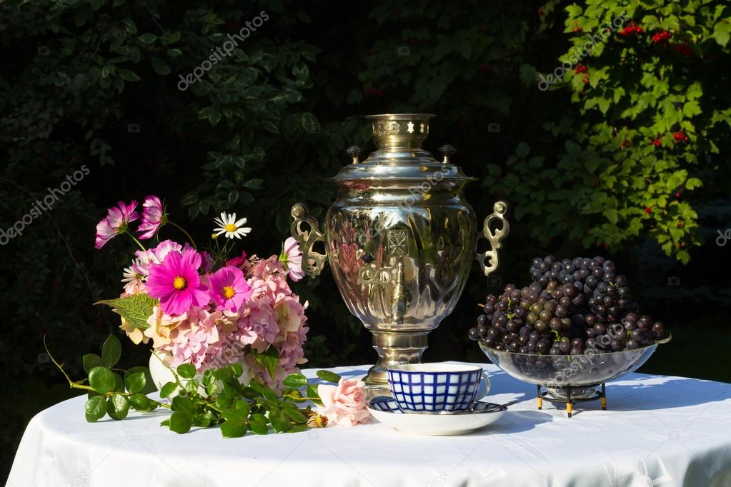 Samovar, cups of tea, pink flowers and grapes on a table covered
