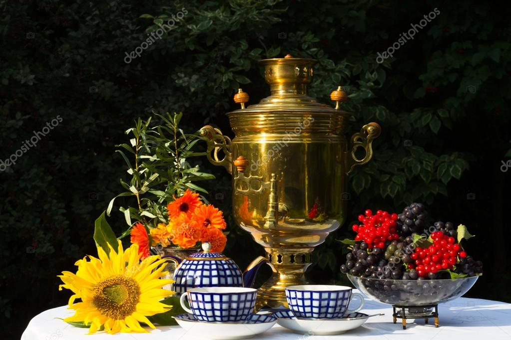Samovar, cups of tea, red flowers with branches buckthorn, flower