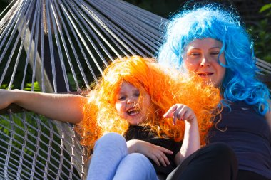 Portrait of a little girl in the carnival wig of hair color in t