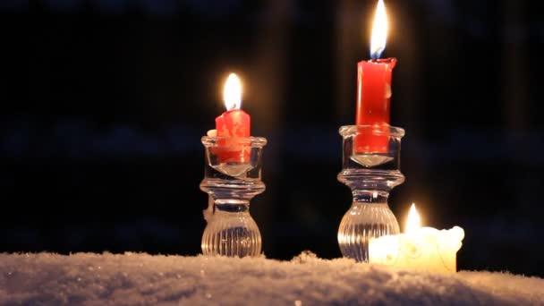 Candele rosse, candelabri di cristallo e una candela grande stand nella neve e la masterizzazione. È freddo e buio. La neve è i piccoli fiocchi di neve, cade rigido. La sensazione di inverno, vacanza, Natale e Capodanno