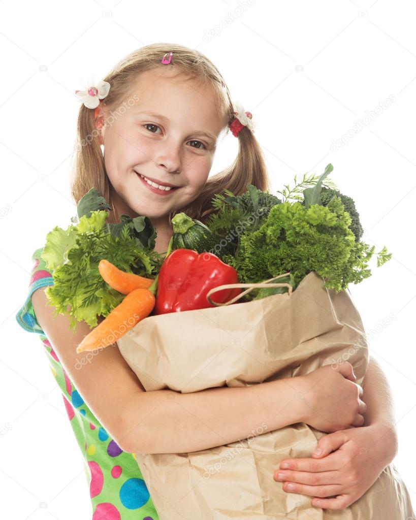 Sweet girl with a paper bag with vegetables