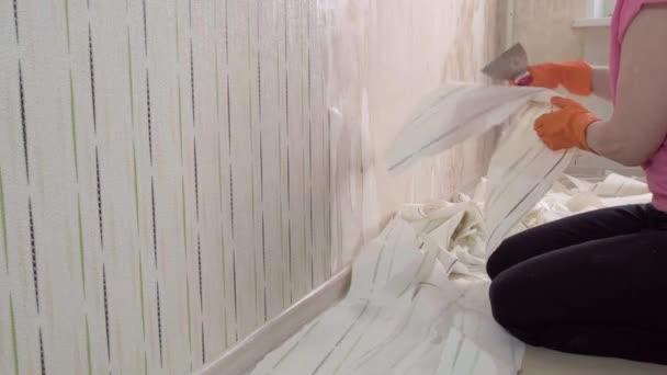 Dospělá žena sundá tapetu a v pokoji pracuje s obracečkou..