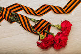Photo St. George ribbon and carnations on wooden background