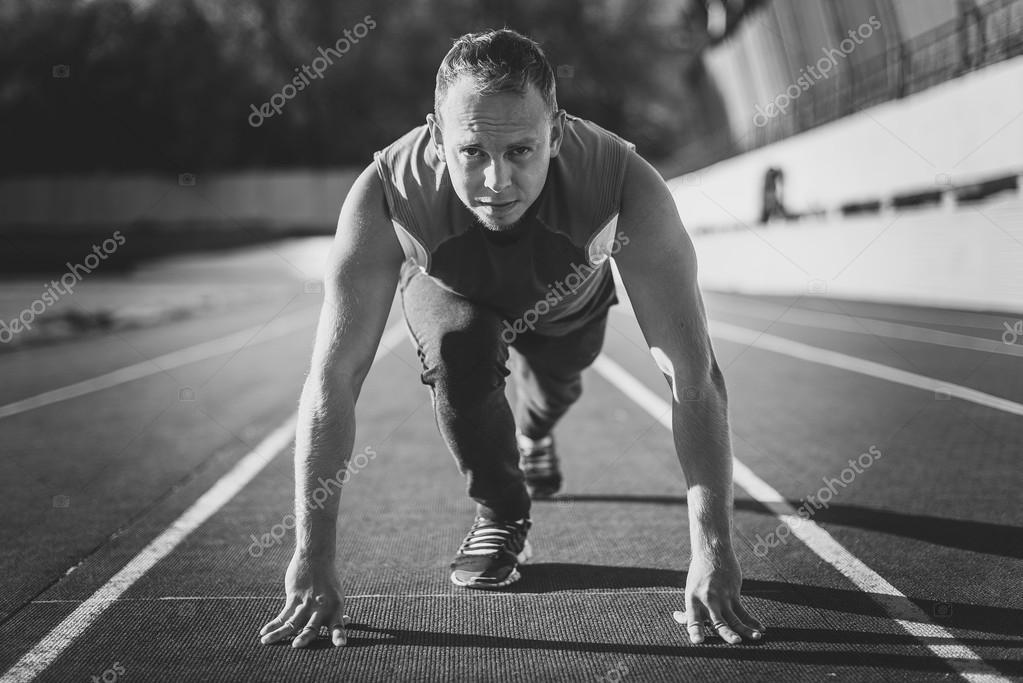 a1c3d8a0785 Atletisk man står i en hållning redo att springa på ett löpband — Foto av  ...