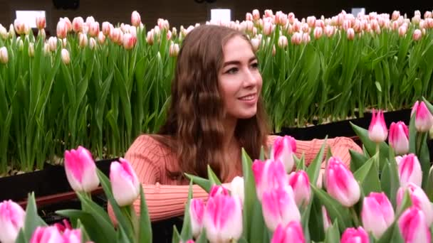 Young girl in a brown dress posing in a greenhouse of flowers Tulips