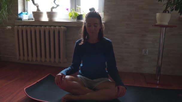 Gyönyörű fiatal nő otthon meditál. Lány vesz mély lélegzetet és pihentető jóga Mate Feel Stressz mentes otthon egyedül.