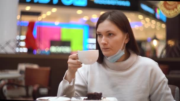 Woman with deflated protective mask drinks coffee in a cafe in a shopping mall