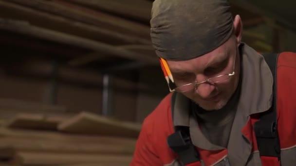 Tischler steht hinter dem Arbeitsplatz, verarbeitet Holz mit Spezialgeräten