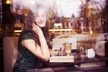 Brunette woman sitting at the cafe reading book, studing and drinking coffee and talking on the phone. Copy Space