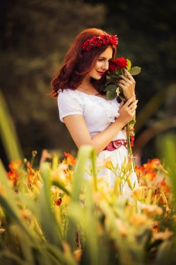 Beautiful brunette caucasian woman in white dress at the park in red and yellow flowers on a summer sunset holding roses