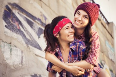 Two Brunette teenage girls friends in hipster outfit (jeans shorts, keds, plaid shirt, hat) with a skateboard at the park outdoors. Copy space