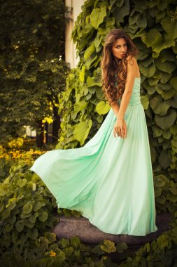Beautiful blonde with a long curly hair in a long evening dress in motion outdoors near retro vintage building all in leaves in summer sunset