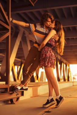 Young couple kissing in the flares of sunset light on a bridge c