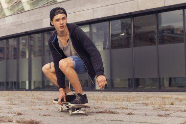 Young blonde guy on skateboard in casual outfit in the urban cit