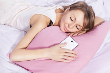 Beautiful blonde woman sleeping with a phone in her hand, waitin