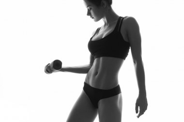 Sexy slim fit woman body with dumbbells. Muscled abdomen. Sports