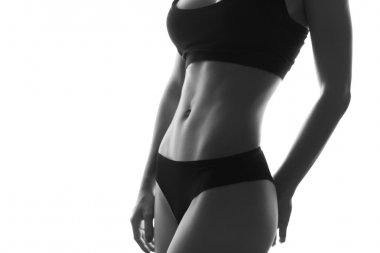 Sexy slim fit woman body abs. Muscled abdomen. Sportswear. Isola