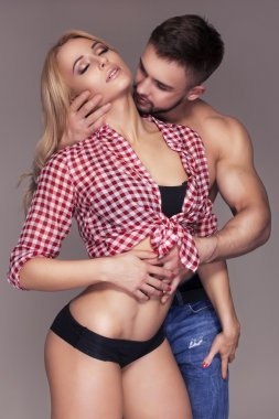 Sexy fit muscled couple in jeans and pants and plaid t-shirt on
