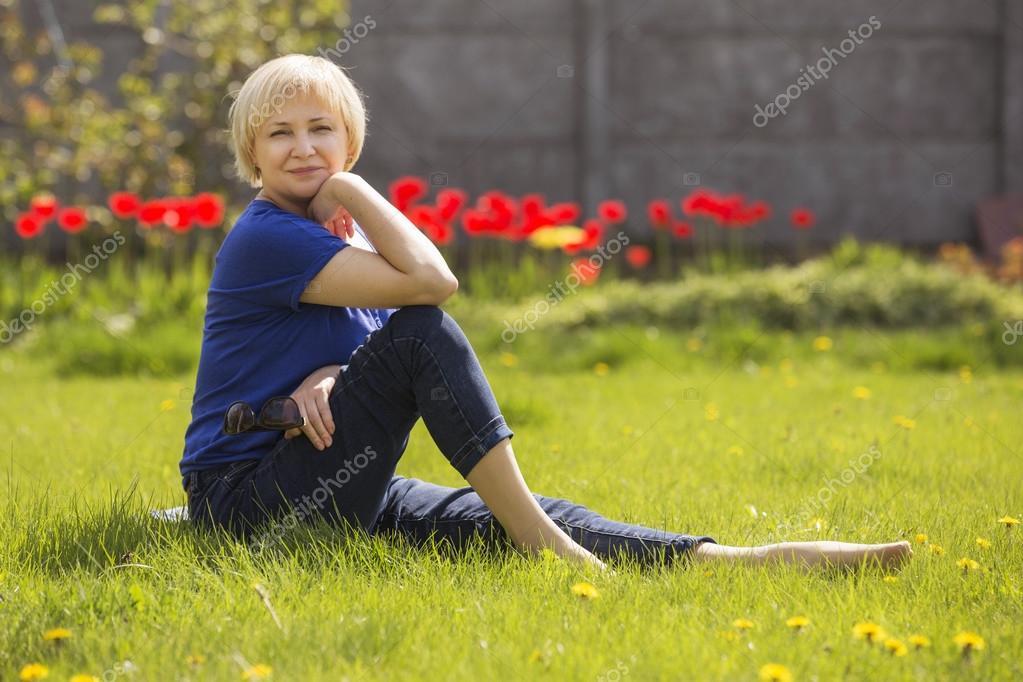 Beautiful blonde eldery senior woman relaxing on a grass in back