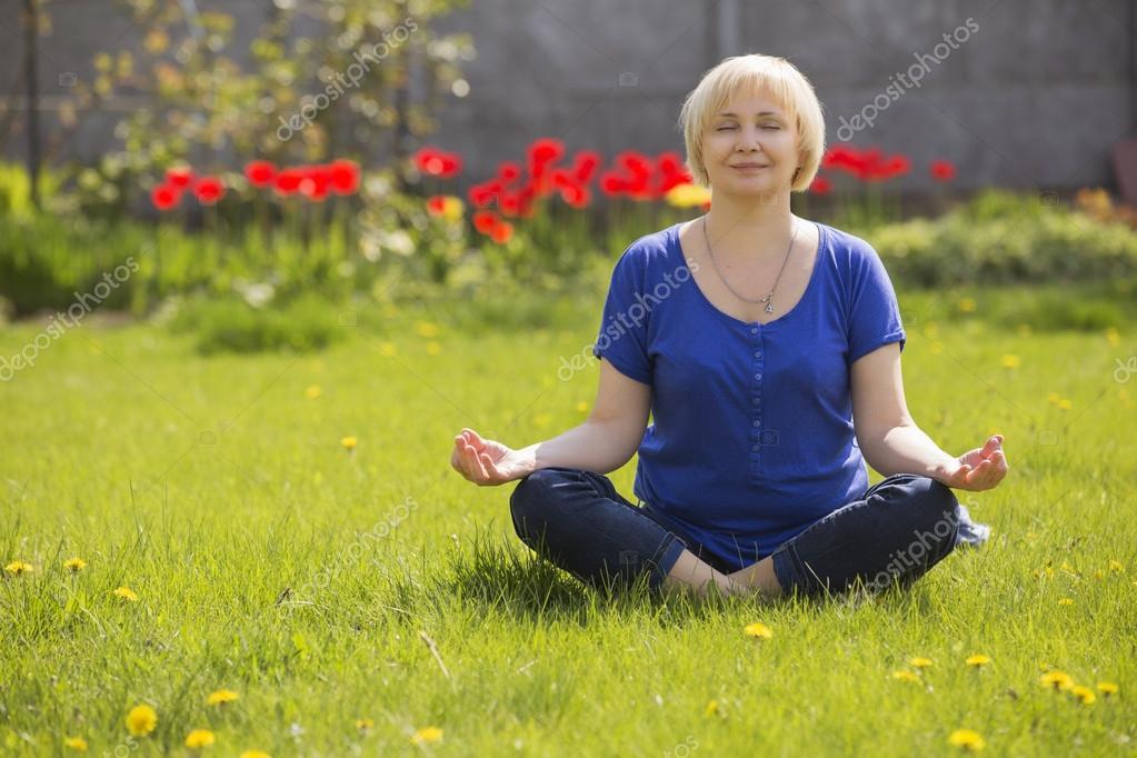 Beautiful blonde eldery senior woman relaxing on a grass in park