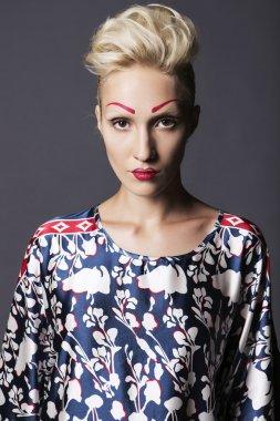 Young blonde transgender woman model in long blue pattern dress,