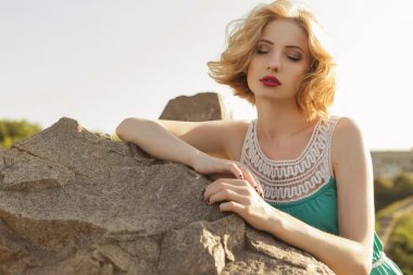 Beautiful blonde woman with curly short bob hairstyle, delicate