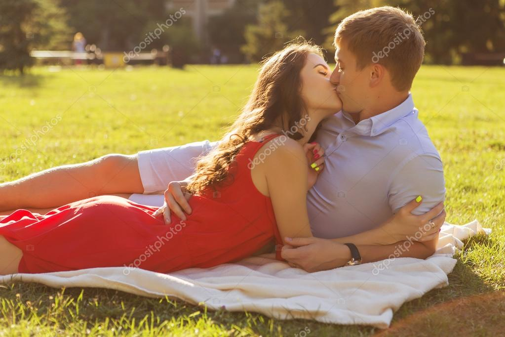 Beautiful brunette couple in love kissing on a date in the park.