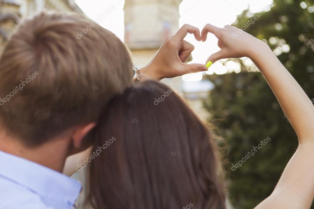 Beautiful brunette couple in love kissing on a date in the park,
