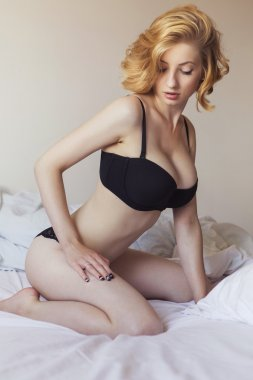 Beautiful blonde fit woman with make up and curly short hairstyl