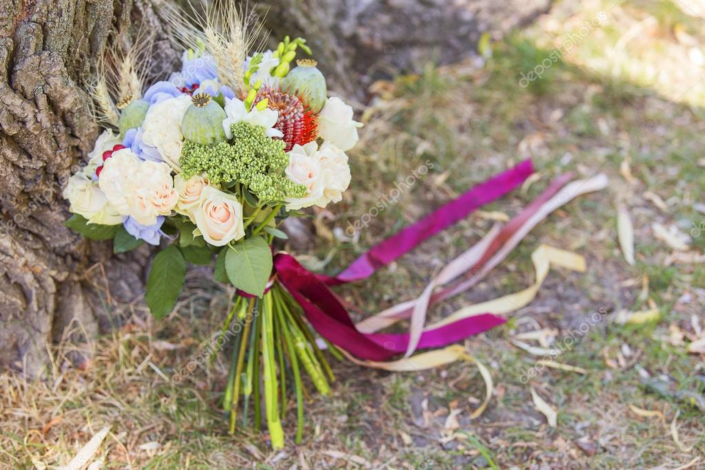 Wedding bouquet of summer flowers laying on green grass. Spring ...