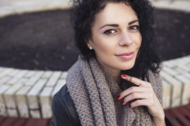 Beautifil brunette caucasian woman in leather jacket and scarf w