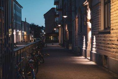 "Картина, постер, плакат, фотообои ""scenic view of the evening street in stockholm. bicycles are parked along the fence."", артикул 426641942"