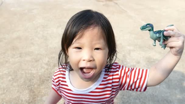 Little girl playing with dinosaur toy