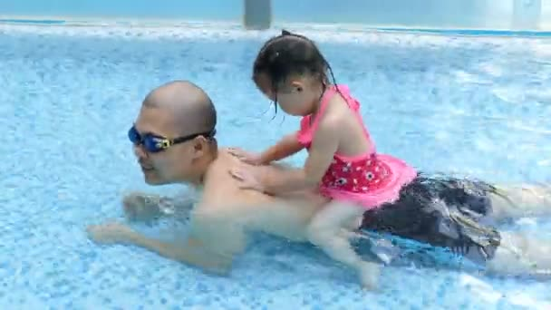 father and daughter play in swimming pool